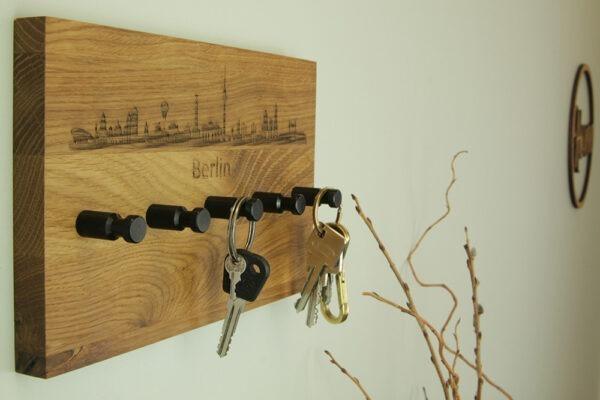 Schlüsselbrett mit schwarzen Haken und Silhouette der Stadt
